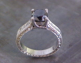 custom engagement ring with large black diamond and intricate band engraving top view