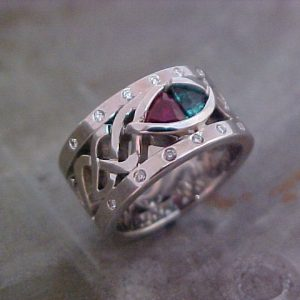 custom white gold ring with celtic engraving and ruby and emerald center gems