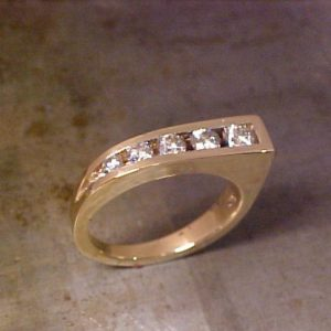 custom wedding ring in yellow gold with diamonds in a unique shape
