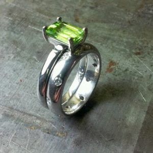slim band ring with large green sapphire and matching wedding band