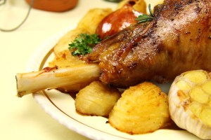 Roasted lamb leg with bone and baked vegetables.