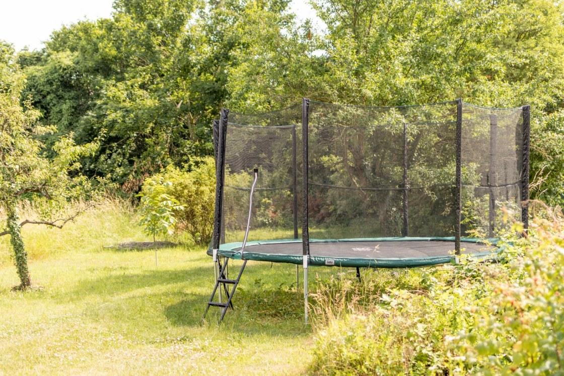 Großes Trampolin im hinteren Teil des Gartens der Ferienhäuser