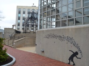 Two Jef Aérosol stencils are parallel to each other, near the west entrance into Richardson Plaza and the clock tower.