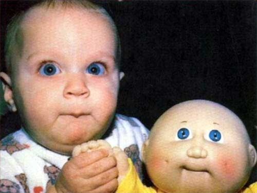 baby-looking-like-his-doll