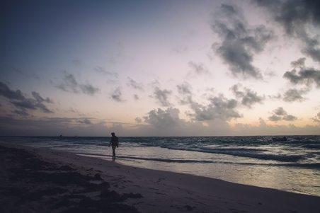 einsamer spaziergaenger am strand von tulum bei sonnenaufgang