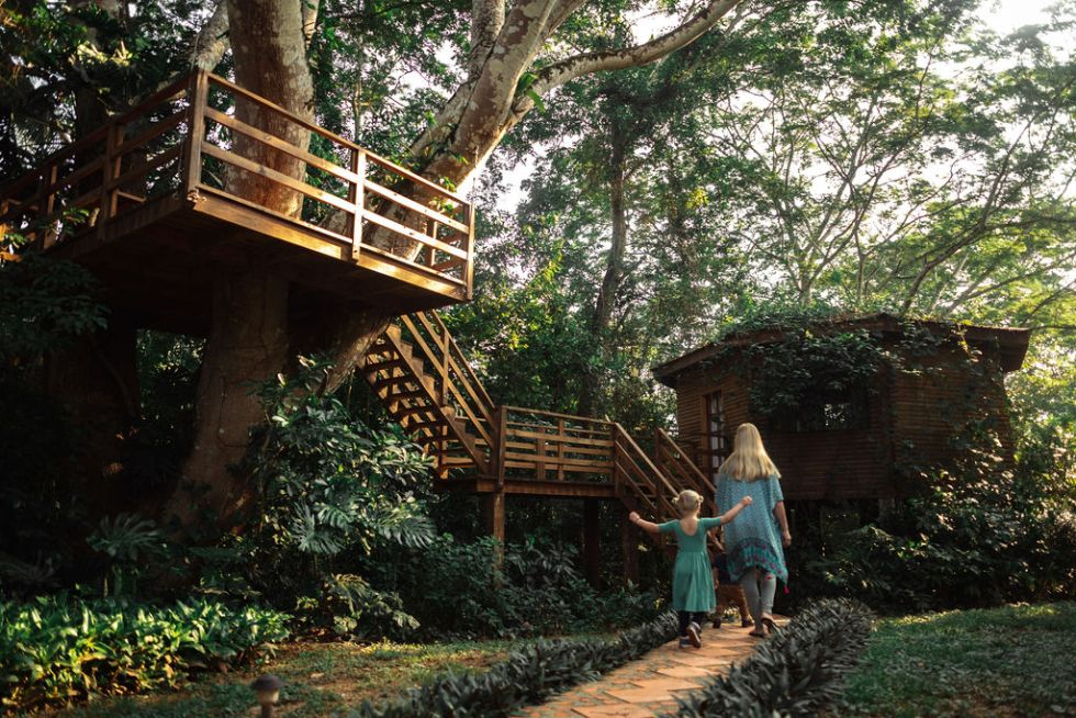 Mother and daughter walking down a path towards a treehouse in the jungle