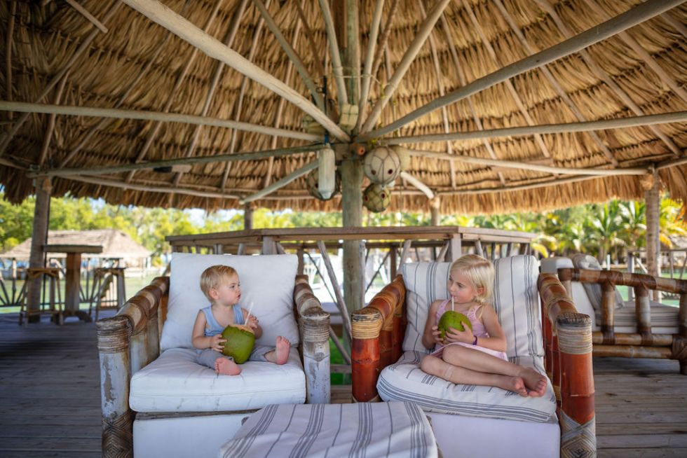 Two kids drinking fresh coconuts with reusable straws in an overwater bungalow on Thatch Caye island in Belize