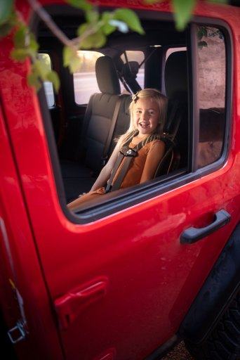 Toddler girl sitting in WAYB Pico Travel Car Seat in red Jeep Rubicon