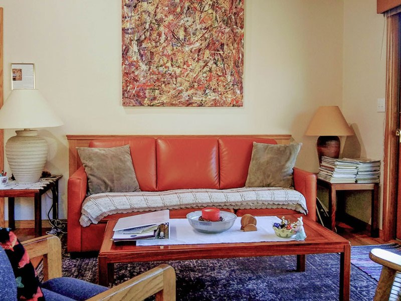 orange couch in living room with table of books and candle
