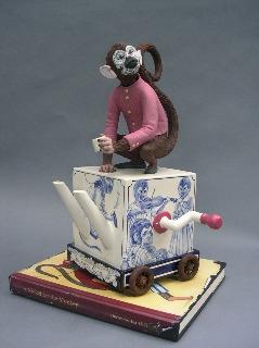 "Red Weldon Sandlin, ""The Hurtea Gurdy Tales: A Nickel for the Monkey"" 2006, ceramic, wood, acrylic paint, 16.5 x 11.5 x 11"", book 1 x 12 x 9""."
