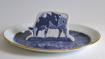 "Paul Scott, ""Scott's Cumbrian Blue(s), Crooklands Cow in a Meadow No. 3,"" 2015, glaze, decal, gold, cow: 5.5 x 8.25 x 1.75, oval platter: 11.5 x 16.5 x 1.5""."