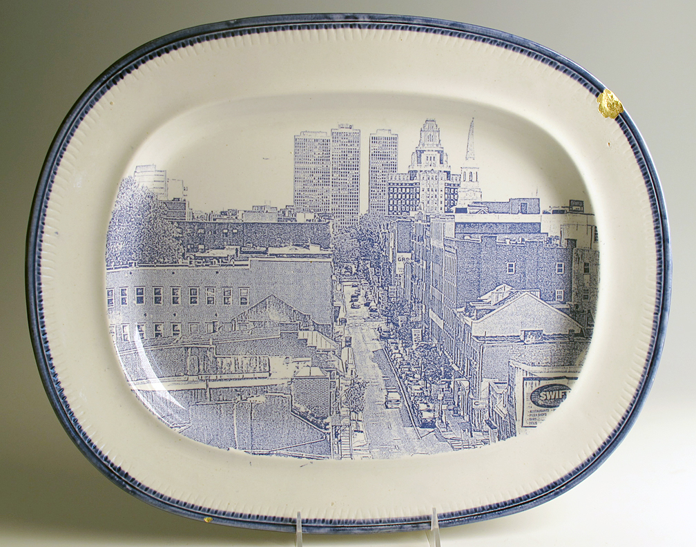 """Paul Scott, """"Cumbrian Blue(s), American Scenery, Philadelphia"""" 2013, Inglaze decal collage, gold luster on feather edged Pearlware plate c. 1830, 14 x 17.25 x 5"""". Newark Museum Collection."""