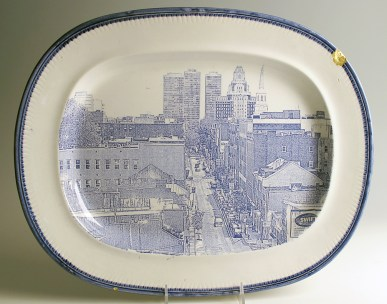 "Paul Scott, ""Cumbrian Blue(s), American Scenery, Philadelphia"" 2013, Inglaze decal collage, gold luster on feather edged Pearlware plate c. 1830, 14 x 17.25 x 5"". Newark Museum Collection."