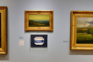 "Mount Holyoke College Art Museum: (right) George Inness, American (1825-1894), ""Saco Ford: Conway Meadows"" 1876, oil on canvas. (center top) Homer Dodge Martin, American (1836-1897), ""A Glimpse of Lake Placid,"" 1887, oil on canvas. (center bottom) Paul Scott, ""Scott's Cumbrian Blue(s), American Scenery, Hudson River, Indian Point No. 4, "" 2015, ceramic transfer decal.  (left) Albert Bierstadt, American (1830-1902), ""Hetch Hetchy Canyon,"" 1875, oil on canvas"