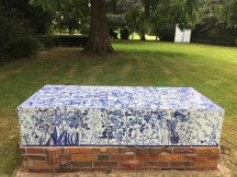 "Paul Scott, ""Scott's Cumbrian Blue(s), A Flowerbed for Alice,"" 2016, in-glaze decal collage on porcelain tiles on a brick structure by Lillemor Petersson. Guldagergård, Skælskør Bygarden, Denmark, 80 x 35.5 x 27.5"""