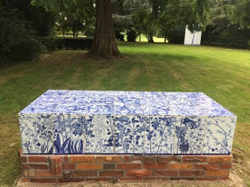 "Paul Scott, ""Scott's Cumbrian Blue(s), A Flowerbed for Alice,"" 2016, in-glaze decal collage on porcelain tiles on a brick structure by Lillemor Petersson. Guldagergård, Skælskør Bygarden, Denmark, 80 x 35.5 x 27.5""."