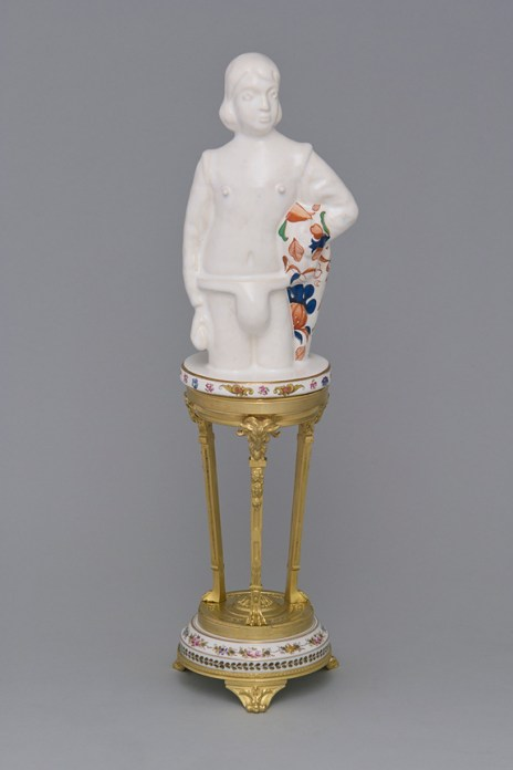 "Leopold Foulem, ""Boy with Cape on Empire Style Stand"" 2012, ceramic, found object, decal, gold luster, 16.5 x 5 x 4.5"". Courtesy of David Kaye Gallery"