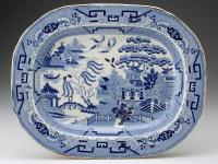 """Paul Scott, """"Cumbrian Blue(s) - A Willow for Ai Weiwei, Wen Tao, Liu Zhenggang, Zhang Jinsong, Hu Mingfen"""" 2012, in-glaze decals on partially erased Willow Pattern platter (c.1840), 13.75 x 17""""."""