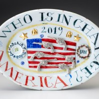 "Mara Superior, ""Who is in Charge, America?"", 2019, high-fired porcelain, ceramic oxides, underglaze, glaze, overglaze enamel, gold leaf, 6.5 x 9.5 x 1''."