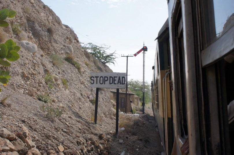 """Den Bolanpass hinunter: Um sicher zu sein, dass die Bremsen des Zuges funktionieren, muss der Zug an bestimmten Stellen, wie hier an der Tafel """"STOP DEAD"""", anhalten. Falls er das nicht tut, wird er auf das ins Niemandsland führende Stumpfgleis geschickt"""