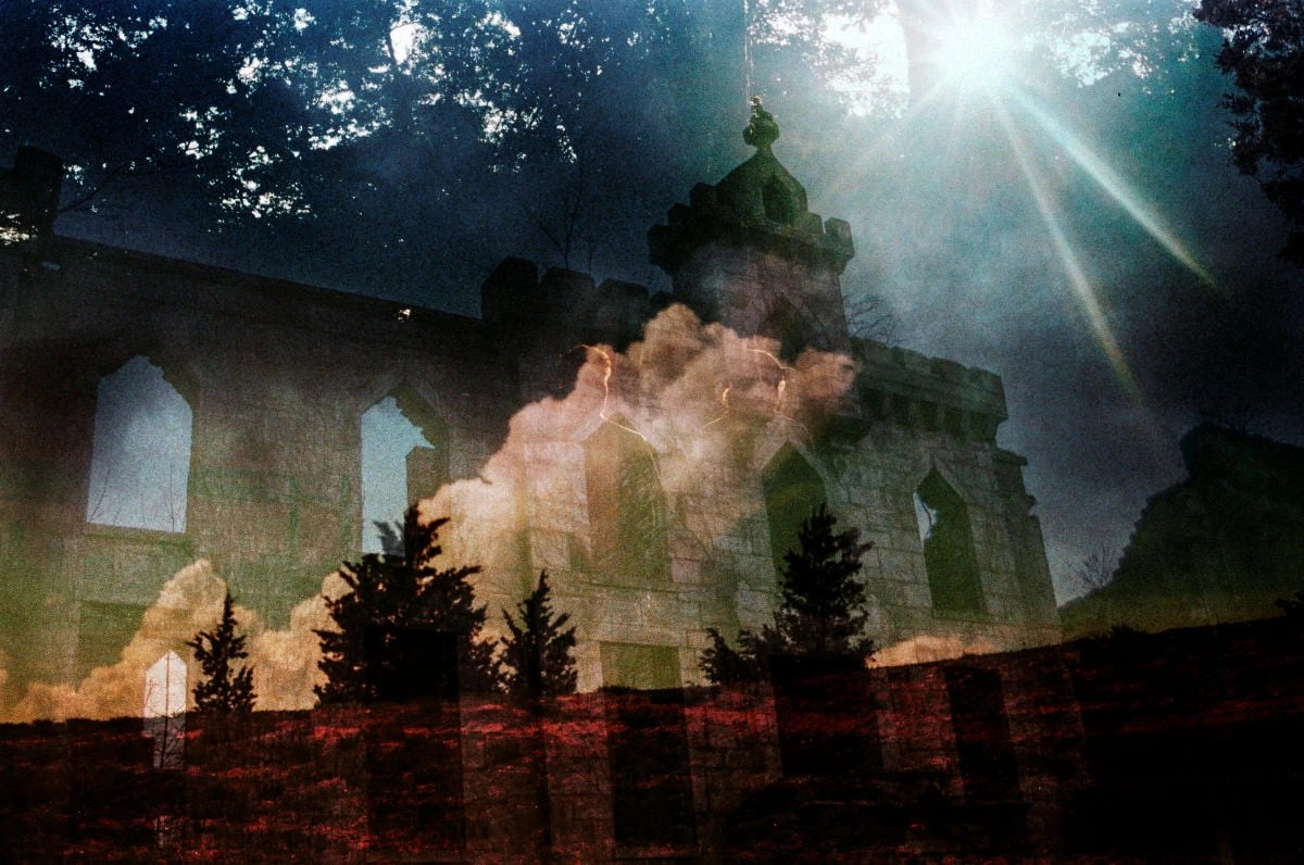A photographic print of a gothic cathedral shot from an ant's eye view. The print has several images layered, all of which are translucent. Over the cathedral is a large white cloud and in the foreground there are four pine trees, which are a dark red. The background is a dense forest canopy with spots of light trickling through the leaves.