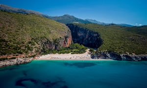 Adriatic beach in Albania surrounded by green hills where the Kala music festival is held.