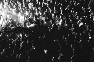 May be a black-and-white image of 7 people and crowd