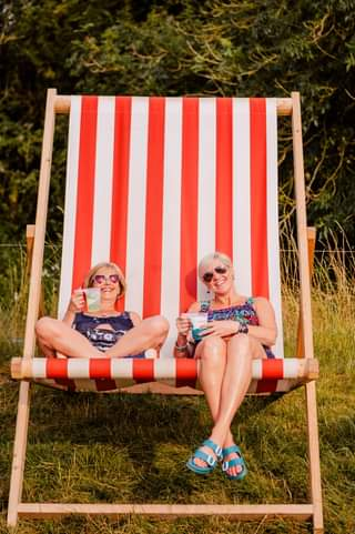May be an image of 2 people, people sitting, stripes and outdoors