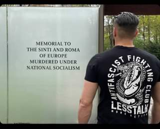 """May be an image of one or more people and text that says """"S MEMORIAL TO THE SINTI AND ROMA OF EUROPE MURDERED UNDER NATIONAL SOCIALISM NTIFASCIST NTIFASC AN FIG F ING LESSTALK CLUBNS CLUB MORE CT"""""""