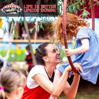 """May be an image of child, standing, outdoors and text that says """"SHOWTIME CIRCUS LIFE IS BETTER UPSIDE DOWN!"""""""