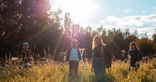 May be an image of 2 people, child, people standing, grass, nature and tree