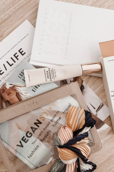 Makeup tube, tube packaging, purse,scarf, magazine, and book on a wooden table
