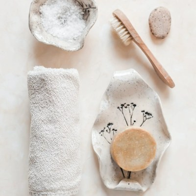 Elements of an organic skincare routine - a cotton towel, bath salts, a brush, a pumice and organic soap.