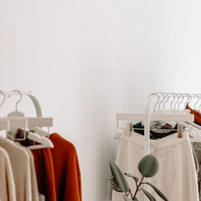 Cream- and rust-colured clothing hung on two clothes racks