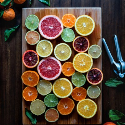 Assorted sliced citrus fruits on a brown wooden chopping board