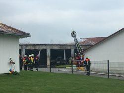 Brennende Lagerhalle in Hohenreichen mit Feuerwehrleuten, Drehleiter und ausgebranntem Teleskoplader.