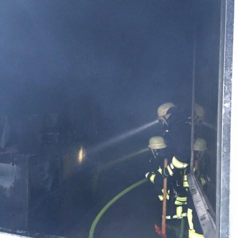 Feuerwehrleute durch ein geöffnetes Fenster des Brandhauses in der Staatlichen Feuerwehrschule Würzburg betrachtet, während sie den Raum absuchen.