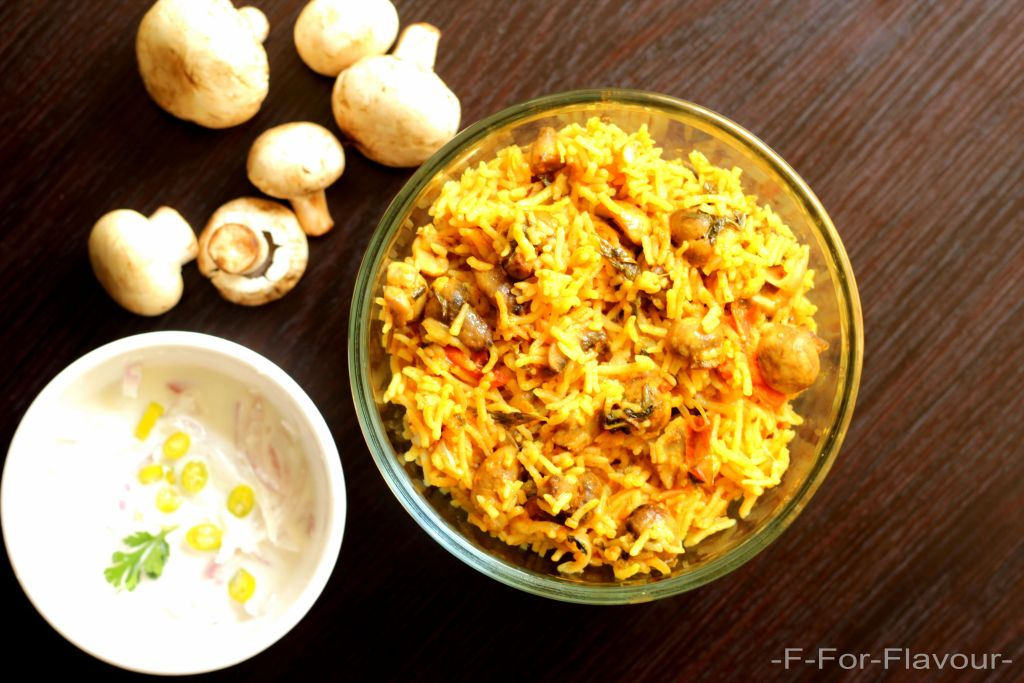 Mushroom Biryani in a bowl with onion raitha
