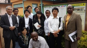 The group posed in front of the Riruta Health Centre, together with (back row from right to left) Mr. Joseph Kagiri from Pricewaterhouse Coopers (representing the Kenya country mechanism team of the Global Fund), Dr. Osamu Kunii of the Global Fund, Sister Wanjiru Kimita, the nursing officer in charge, and the delegation (with the group's advisor Prof. Satoru Watanabe).