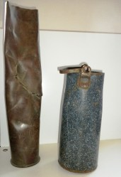 Größenvergleich: Granathülse 8,8 cm (Übungsmunition, 57 cm hoch), Milchkanne, Kaliber 12,8 cm, 37 cm hoch.
