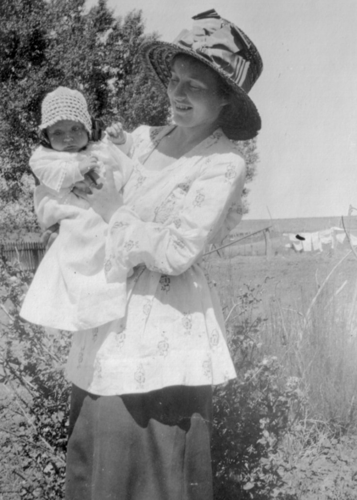 Woman holds baby outside