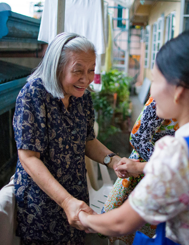 An elderly woman smiles at another woman