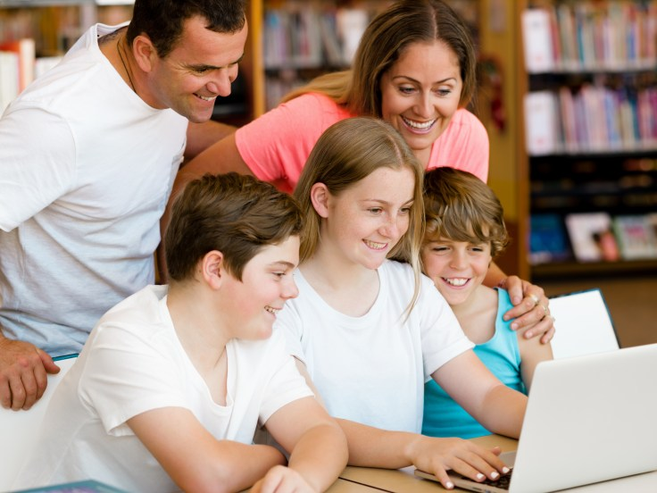 A smiling family gathers around a computer at a library.