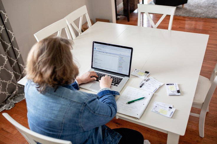 a woman writes on her computer