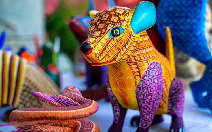 A colorful sculpture of an animal, known as an alebrijes, a colorful tradition of Mexico