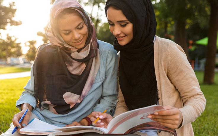 Two women write in a book.