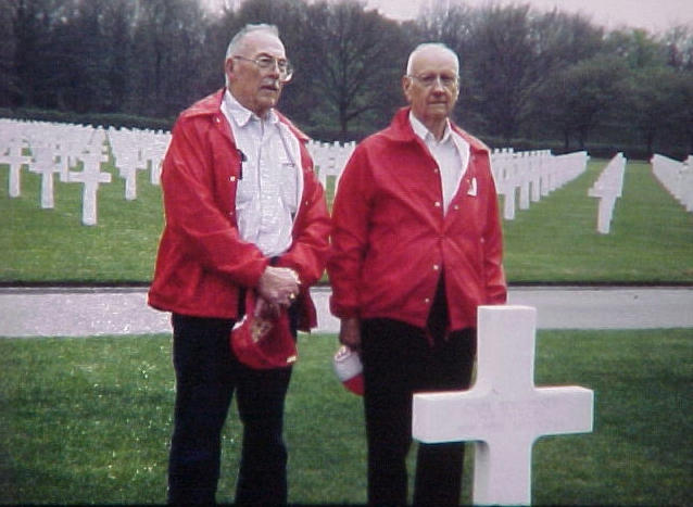Two men of the 951st battalion at a grave for one of their battalion members.