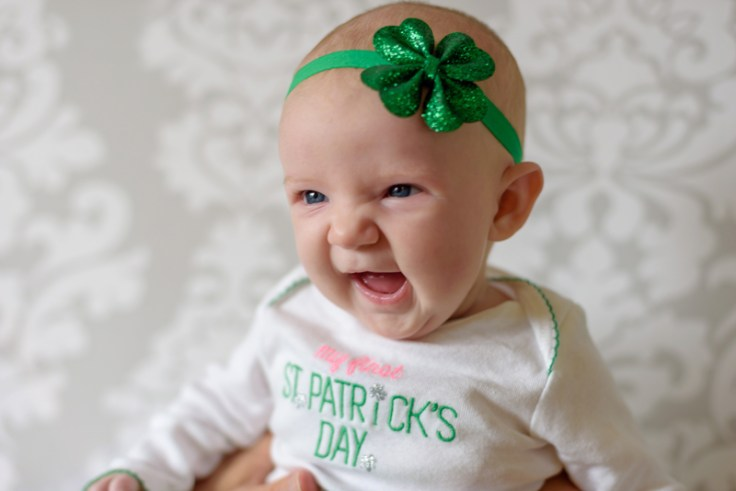a little girl with a shamrock headband