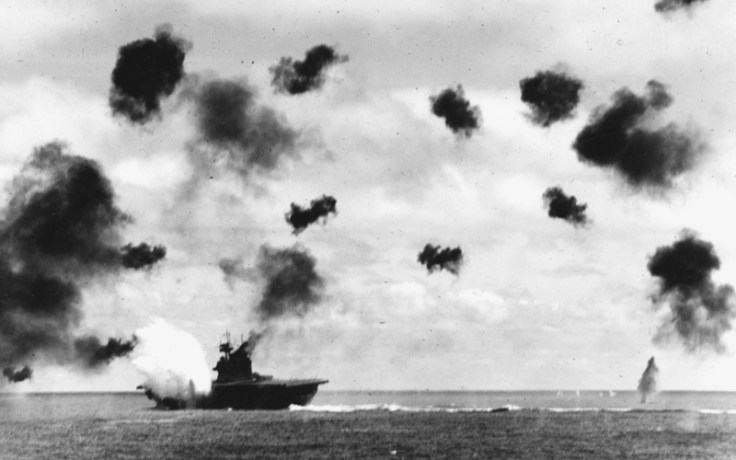 Warship on water with smoke in sky