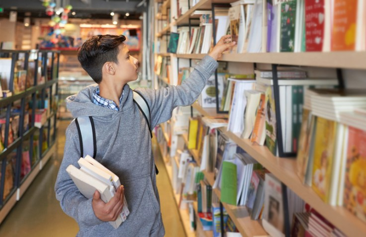 Boy looking at library books.